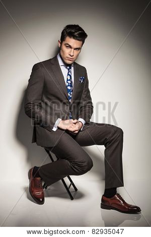 Full body picture of a young business man holding his hands together while sitting on a stool. Against grey studio background.