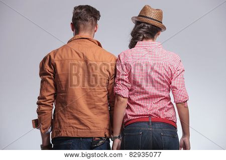 Rear view of a young couple posing on grey studion background.