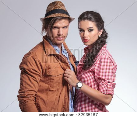 Close up picture of a young beautiful woman pulling her boyfriend close to her. Both looking at the camera.