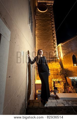 Woman Wearing Black Cocktail Dress Posing Against Ancient Tower