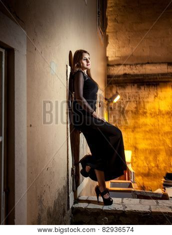 Woman In Long Dress Leaning Against Wall On Old Street At Night