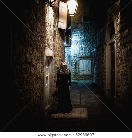 Woman In Long Black Dress Standing Under Lantern At Old Narrow Street