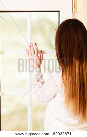 Beautiful Woman Looking Through Window.