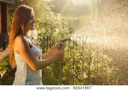Beautiful Brunette Woman Watering Garden Bed With Vegetables