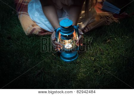Woman Sitting On Grass At Night And Holding Hands On Lantern