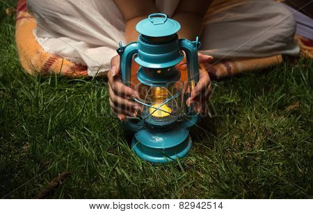 Woman Sitting At Garden At Night And Warming Hands On Lantern