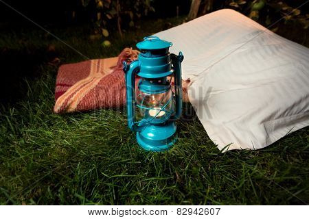 Old Oil Lamp Standing On Grass Next To Pillow And Blanket