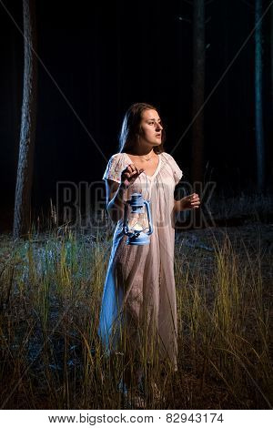 Lost Woman In Forest At Night Walking With Candle Lantern