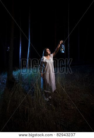 Woman With Gas Lantern Lighting Up Forest At Night
