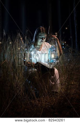 Smiling Woman In Nightgown Sitting At Field At Night And Reading Book