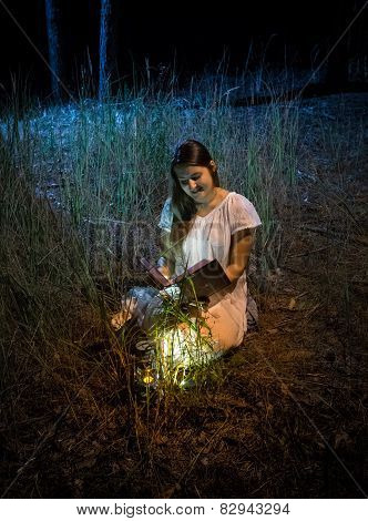 Woman Sitting At Night Forest With Lantern Reading Big Old Book