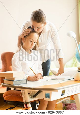 Mother Hugging And Praising Daughter While Doing Homework