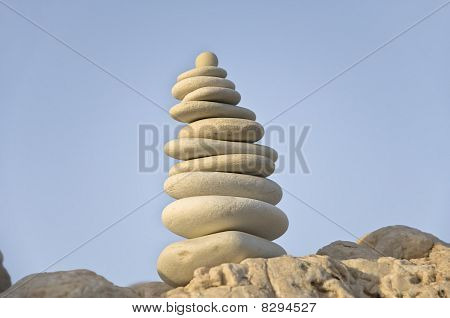 White sea stones pyramid on sky background
