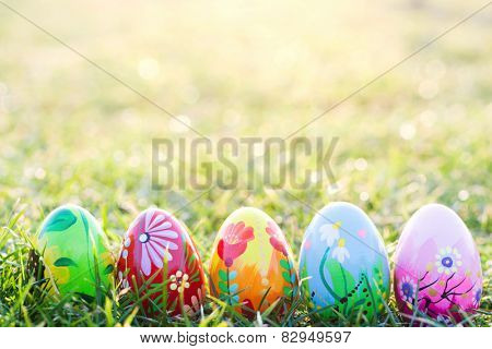 Handmade Easter eggs on grass. Floral, colorful spring patterns and designs. Traditional, artistic and unique.