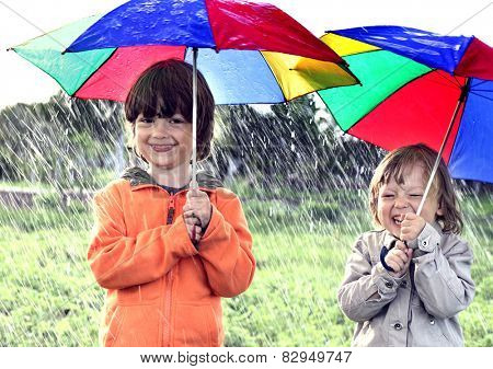 two brothers play in rain outdoors