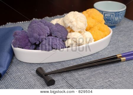 Purple, white and orange cauliflower in white serving dish