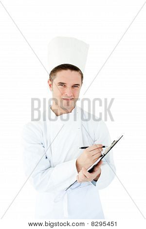 Joyful Young Male Cook Writing On A Clipboard