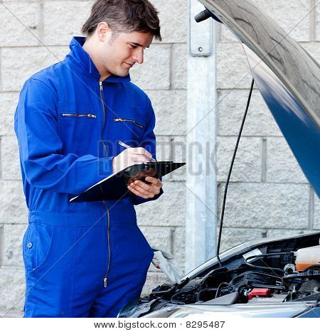 Handsome Mechanic Writing On A Clipboard