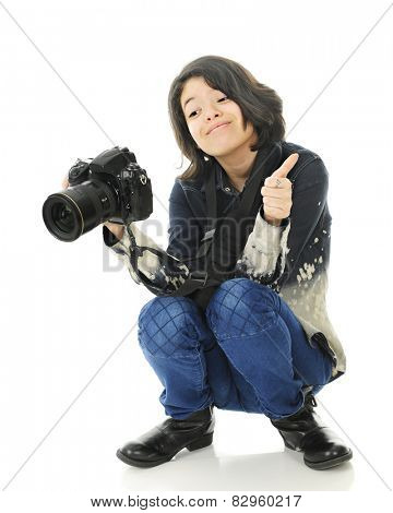 A young teen squatting photographer giving a thumbs up gesture as she looks at the image on the back of her camera.  On a white background.
