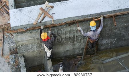 Construction Workers dismantling timber formwork