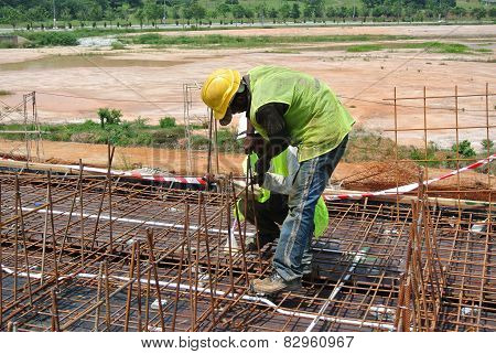 Construction workers fabricating beam reinforcement bar at construction site