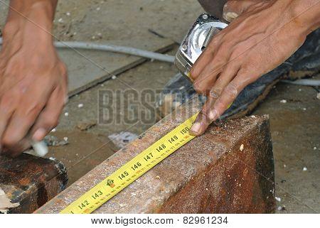 Workers using measuring tape to measure mild steel