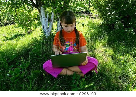 Girl With A Laptop Under The Tree
