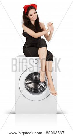 Beautiful Woman Filing her Nails on a Washing Machine