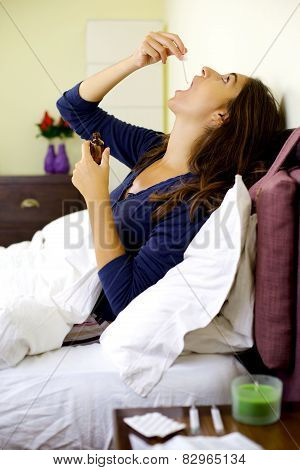 Sick Woman In Bed Taking Medicine