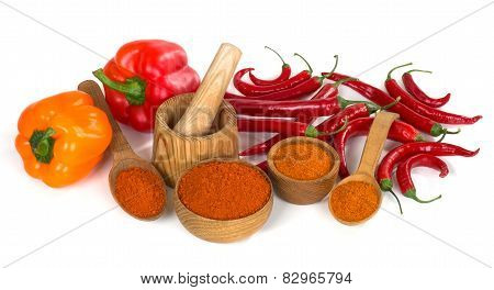 Paprika And Chili Powder Ground In A Wooden Bowl And Spoon On White Background