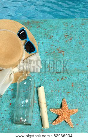 Summer concept with hat, message in a bottle and starfish on grunge deck