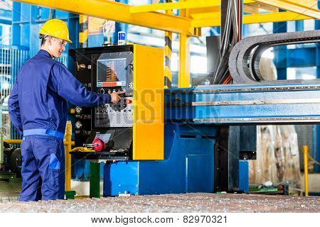 Worker in manufacturing plant at CNC machine control panel
