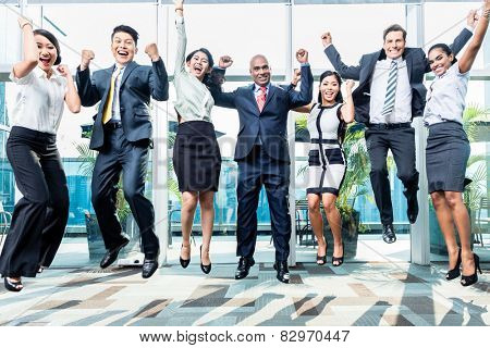 Diversity business team jumping celebrating success, Chinese, Indonesian, Indian, and Caucasian ethnicities