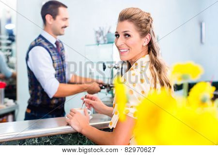 Woman customer ordering espresso or cappuccino at bar counter in coffee shop
