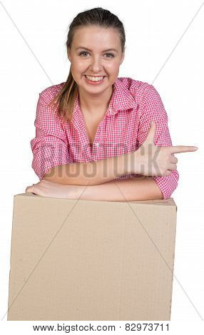 Sexy girl leaning on cardboard box and points finger in the direction