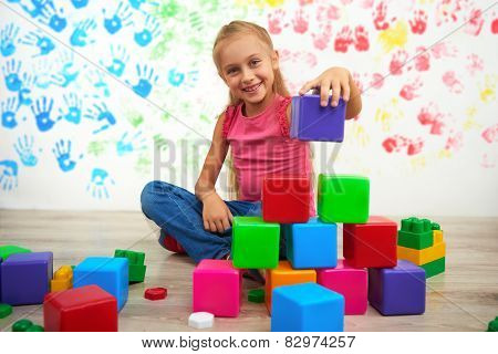 Happy girl making pyramid of colored cubes