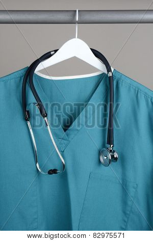 A surgeon's scrubs and stethoscope on hanger against a gray background. Closeup on a white hanger with a gray background in vertical format.