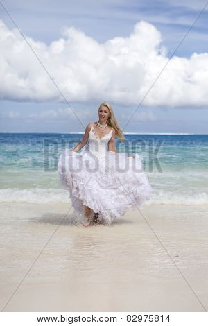 The beautiful woman with a rose runs on the edge of the sea on a beach. Polynesia.