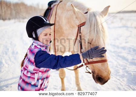 Little girl in jockey helmet touching horse muzzle