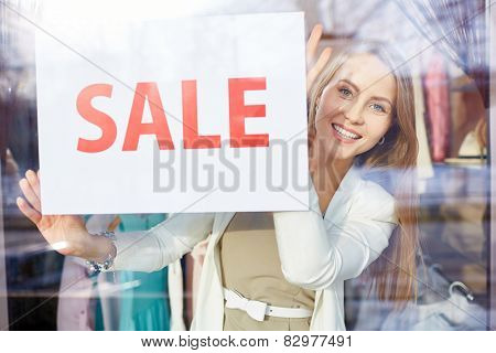 Beautiful young woman announcing sale in boutique