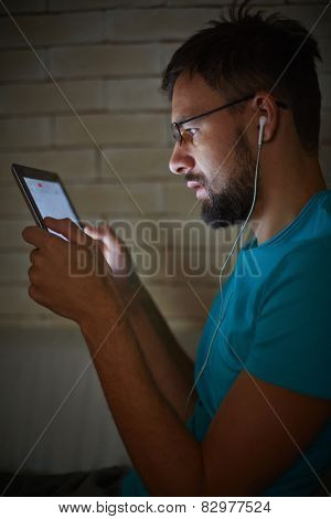 Handsome guy with earphones using touchpad in the dark