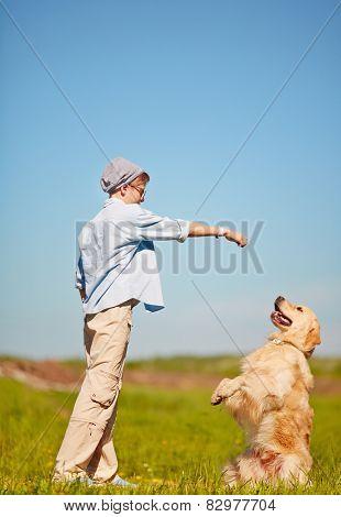 Teenage boy training his pet outdoors