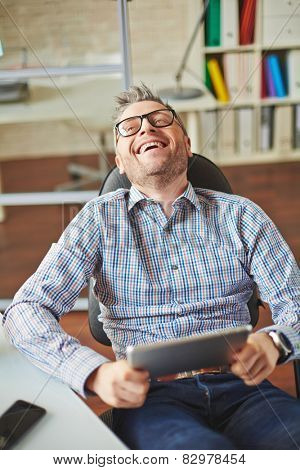 Ecstatic businessman with touchpad sitting by workplace