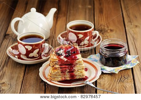Russian Bliny With Currant Jam, Tea Cups, Pot On Wooden Background