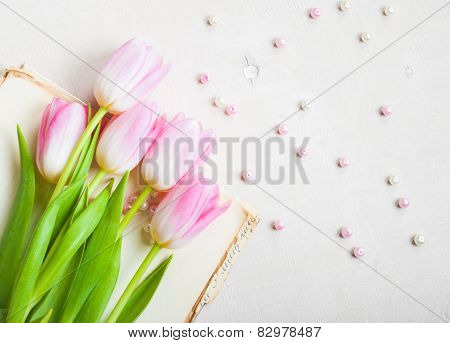 Pink Tulips With Heart And Beads Over White Wooden Table. Closeup