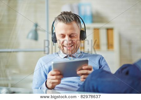 Happy businessman with earphones using touchpad
