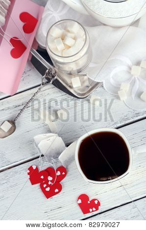 Heart shaped teabag tags, box, teacup on wooden background
