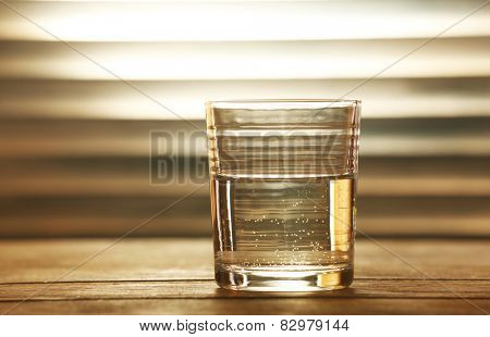 Glass of clean mineral water on wooden surface and planks background