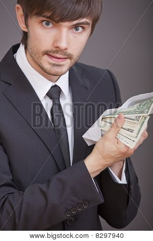 Businessman Holding Dollars In Envelope