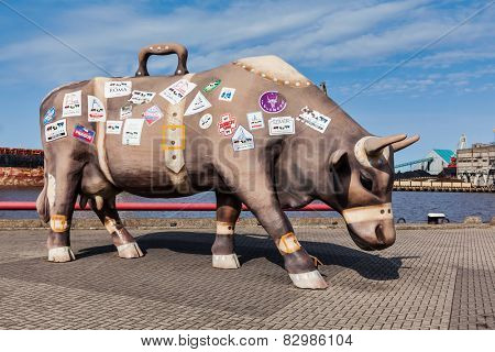 VENTSPILS, LATVIA - MARCH 30, 2014: Traveling Cow's statue. Monument is 4 meters tall and 7 meters long made as a suitcase and sticked by signs of places where Cow parade took place